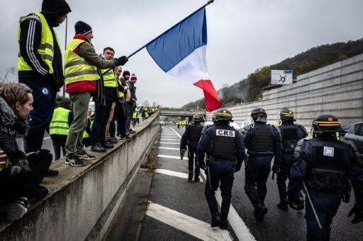 رجال شرطة فرنسيون يصلون لتفريق متظاهرين يرتدون سترات صفراء يرفعون علم فرنسا بين ليون وسانت إتيان في 17 نوفمبر 2018