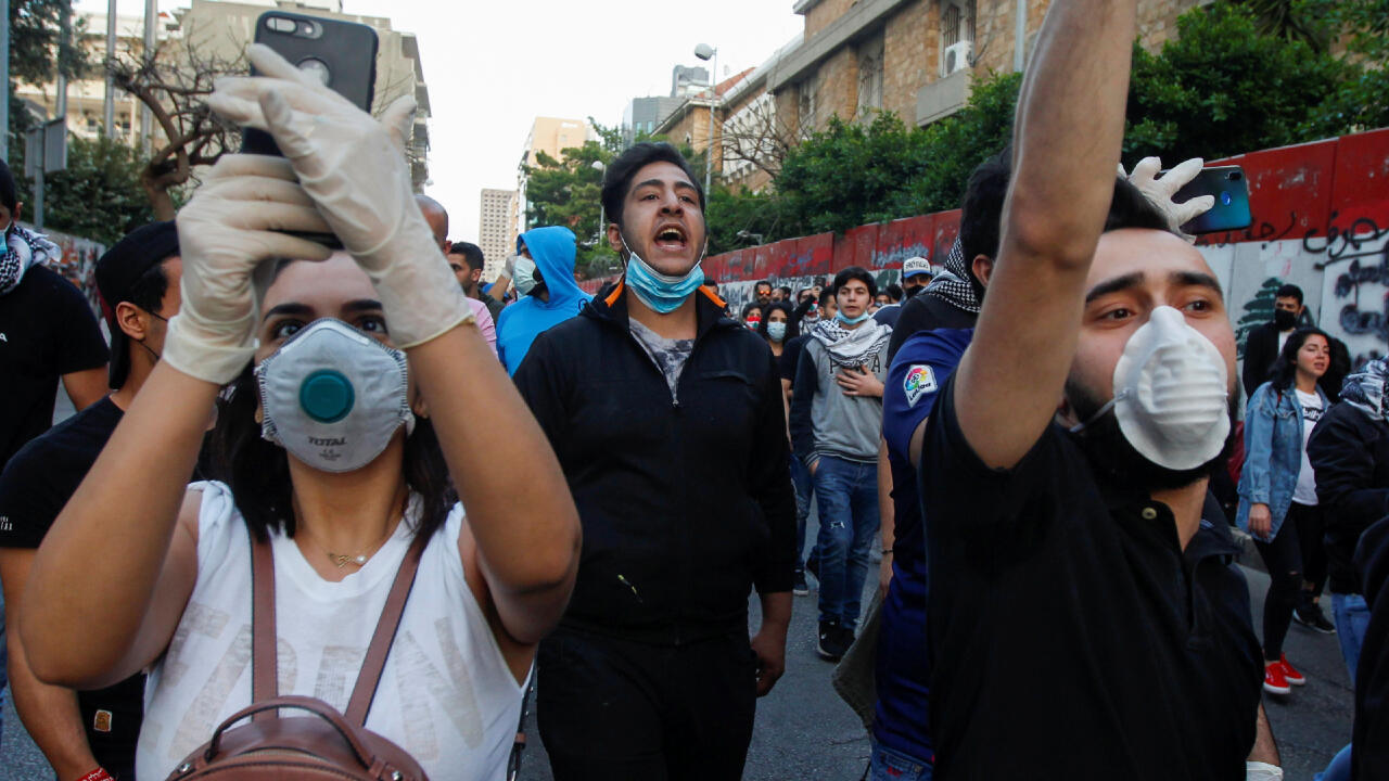 Lebanese demonstrators wear face masks as they chant slogans during a protest against the collapsing Lebanese pound currency outside Lebanon's Central Bank in Beirut, Lebanon April 23, 2020.