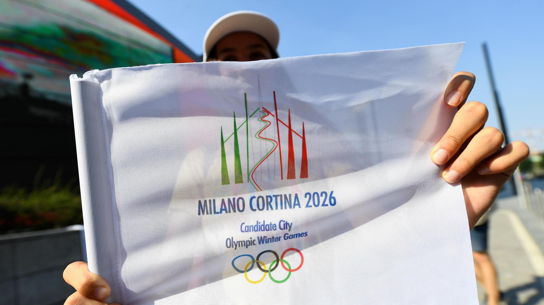 El logotipo de Milán-Cortina d'Ampezzo para los Juegos Olímpicos de Invierno 2026, mientras los italianos celebran la victoria.