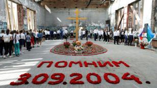 """Residentes de Beslán asistiendo a los actos de conmemoración del aniversario número 15 de la toma de rehenes en la escuela N°1 de esa localidad caucásica. La inscripción dice en ruso """"recordamos 3.09.2004.""""  Beslan, Rusia. Septiembre 2 de 2019."""