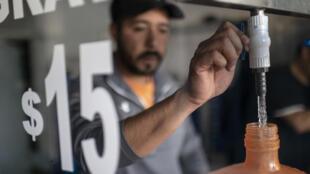 Un empleado de una planta embotelladora de agua de Ciudad de México llena un bidón el 14 de marzo de 2020