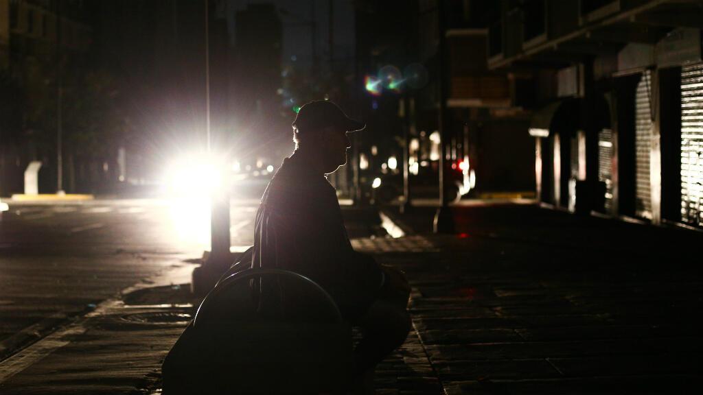 Un hombre se sienta en un banco a oscuras durante un corte de energía en Caracas, Venezuela, el 27 de marzo de 2019.