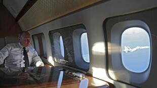 El presidente ruso Vladimir Putin a bordo de un avión, mirando a través de su ventana un avión de combate ruso, mientras viaja a la base aérea de Hamimim en Siria.