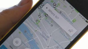 """رجل يحمل هاتفا محمولا يعرض تطبيق """"أوبر"""" في العاصمة البريطانية لندن 22 أيلول/سبتمبر 2017"""