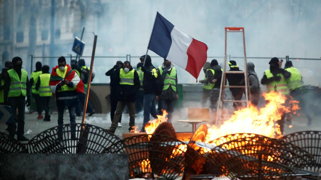 """Los manifestantes que usan chalecos amarillos están parados frente a una barricada mientras se enfrentan con la policía durante los enfrentamientos como parte de un día nacional de protesta del movimiento de """"chalecos amarillos"""" en París, Francia, el 8 de diciembre de 2018."""
