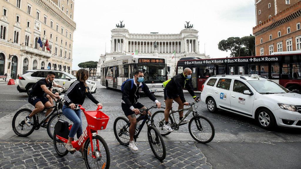 Personas en bicicleta en la Piazza Venezia durante la fase 2 de la lucha contra la pandemia del coronavirus Covid-19 en Roma, Italia, el 9 de mayo de 2020.