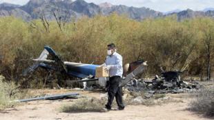 Un homme enquête près de l'épave des deux hélicoptères.