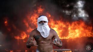 Un manifestante de la oposición con heridas en su cuerpo, hace gestos frente a un autobús en llamas, en Caracas, Venezuela, el 30 de abril de 2019.