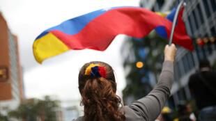 Una partidaria de Guaidó ondea la bandera de Venezuela durante las marchas opositoras a Nicolás Maduro