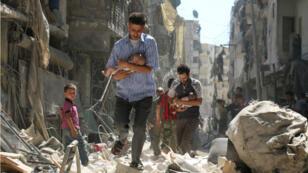 Des civils syriens dans la ville d'Alep, le 11 septembre 2016.