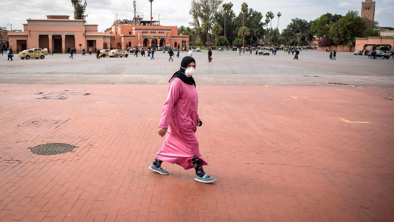 امرأة مغربية ترتدي قناعا واقيا تعبر ساحة جامع الفنا وسط مراكش، 17 مارس/ آذار  2020