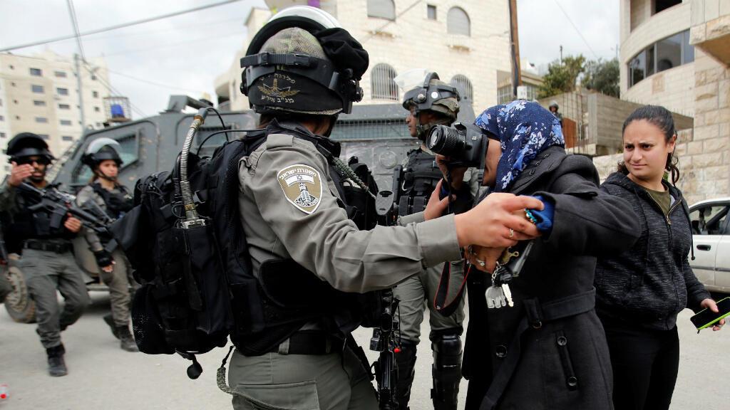 Una fotógrafa local toma fotos a un miembro de la policía israelí, quien intenta detenerla durante la demolición de una casa palestina, cuyos propietarios alegan intromisión de las fuerzas israelíes. Beit Jala, Cisjordania, el 2 de abril de 2019.