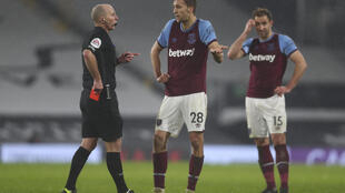 Referee Mike Dean shows West Ham's Tomas Soucek a red card