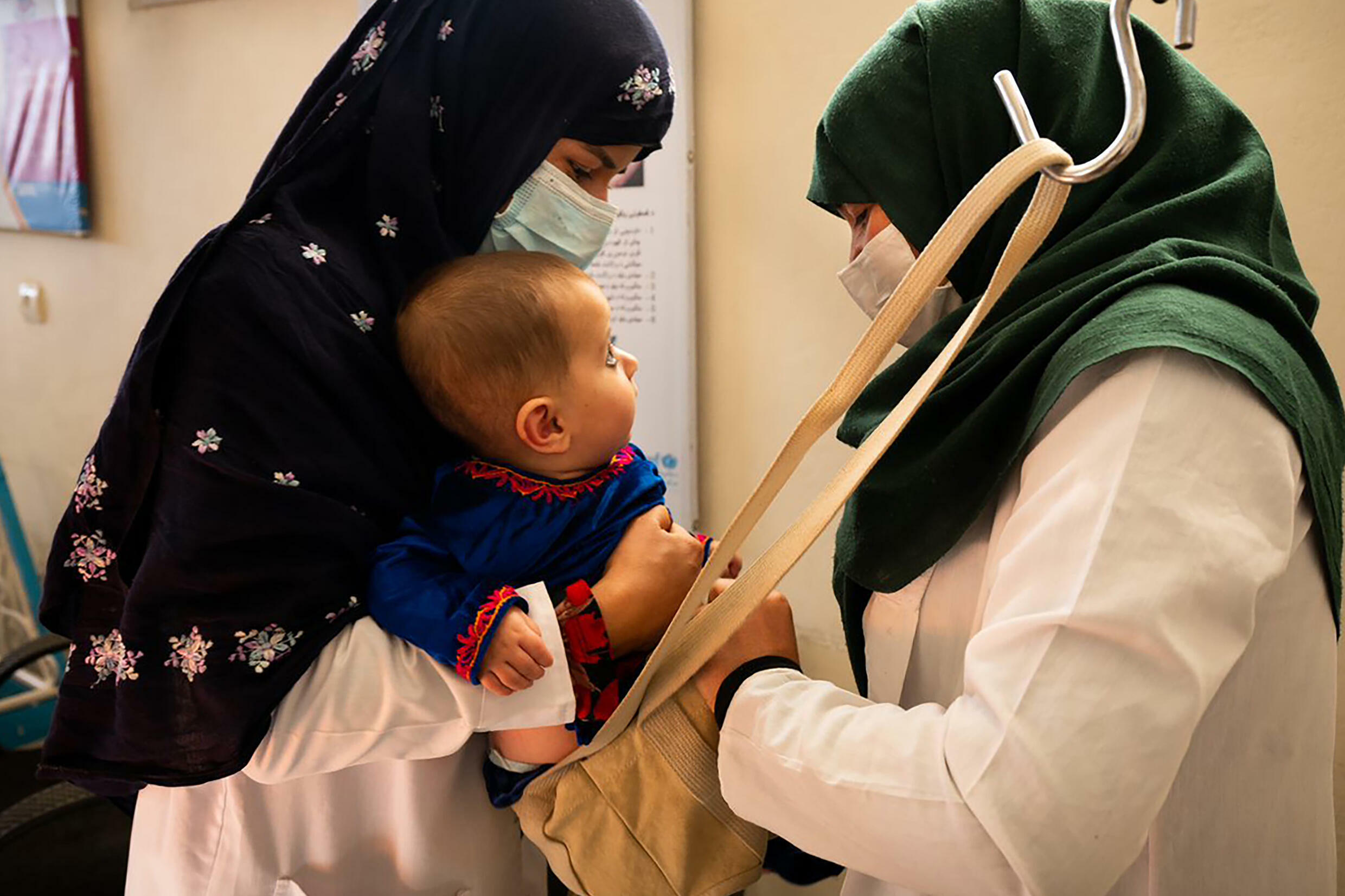 A midwife and a nutrition counsellor weigh a baby at the Tangi Saidan clinic