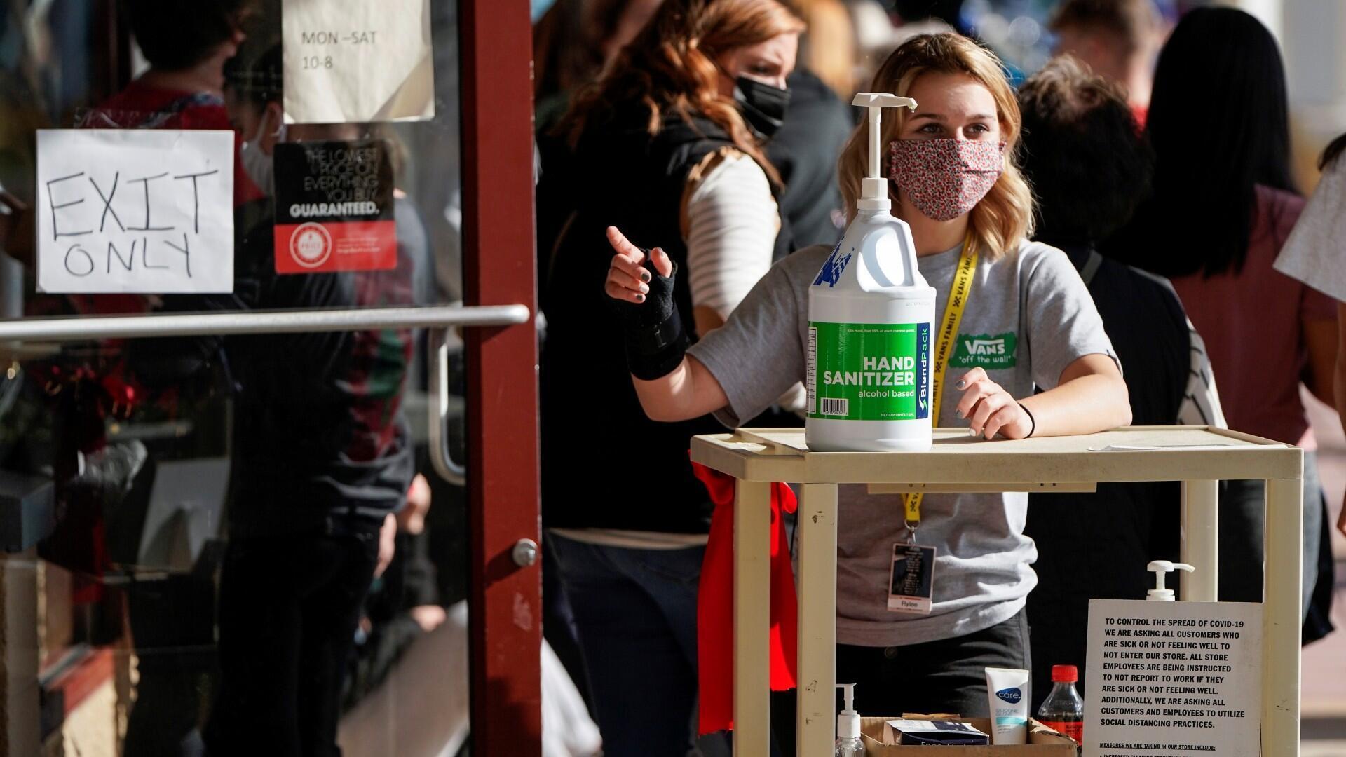 Una mujer cerca de un desinfectante de manos disponible debido a la enfermedad de coronavirus, mientras ayuda a las personas a comprar durante el 'Black Friday' en Rehoboth Beach, Delaware, EE. UU., el 27 de noviembre de 2020.