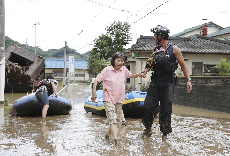 عامل إنقاذ يساعد السكان المحليين في منطقة غمرتها المياه بسبب أمطار غزيرة على طول نهر كوما في هيتويوشي، محافظة كوماموتو، جنوب اليابان، 4 يوليو/ تموز 2020