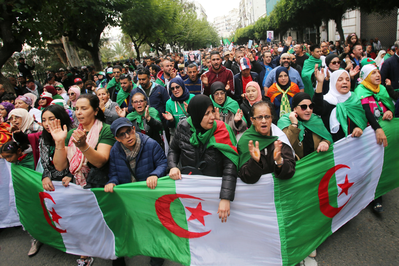 متظاهرون يرفعون العلم الجزائري أثناء مظاهرات ضد الانتخابات الرئاسية. 22 نوفمبر/تشرين الثاني 2019.