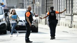 Agentes de policía redirigen el tráfico en la ciudad belga de Lieja cerca del sitio donde un hombre armado disparó y mató a dos policías y un civil antes de ser abatido por la policía, en Lieja, Bélgica el 29 de mayo de 2018.