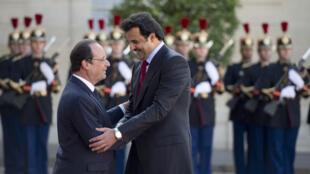 الرئيس الفرنسي هولاند برقفة أمير قطر تميم بن حمد آل ثاني خلال زيارته شهر يونيو 2014