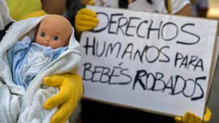 """Des manifestants arborent un poupon et une pancarte réclamant des """"droits"""" pour """"les bébés volés"""" sous la dictature de Franco, à Madrid le 26 juin 2018"""