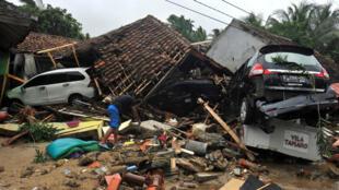 Un residente busca artículos entre las ruinas de una población después de que el área fuera golpeada por un tsunami, en la playa Carita en Pandeglang, provincia de Banten, Indonesia, el 23 de diciembre de 2018.