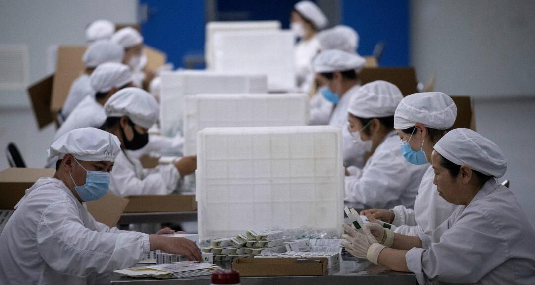 Trabajadores empaquetan la vacuna contra la rabia en un laboratorio de la compañía Yisheng Biopharma, donde los investigadores están tratando de desarrollar una vacuna para el coronavirus en Shenyang, en la provincia nororiental china de Liaoning, el 9 de junio de 2020.