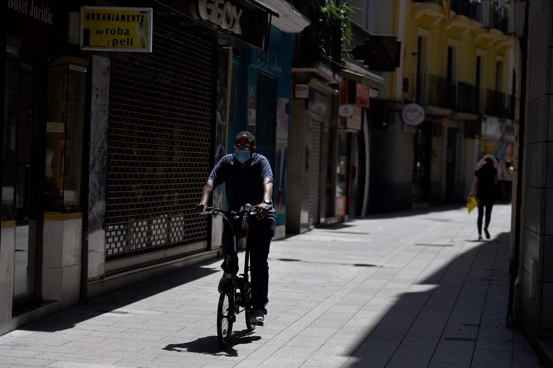 Un homme à vélo portant un masque, dans une rue de Lérida en Espagne, le 13 juillet 2020.