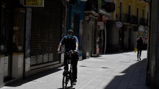 A man wearing a face mask rides a bike in Lerida (Lleida) on July 13, 2020.