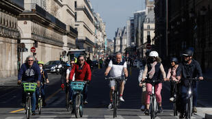 Cyclists ride on the rue de Rivoli in Paris on May 16, 2020, as France eases lockdown measures taken to curb the spread of the Covid-19 pandemic.