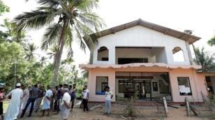 """مسلمون يقفون أمام مسجد """"أبرار"""" الذي تعرض لهجوم بمنطقة كينياما في سريلانكا"""