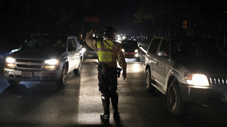 Agentes de la Policía controlan el tráfico a lo largo de una carretera durante el apagón en Caracas, Venezuela, 29 de marzo de 2019.
