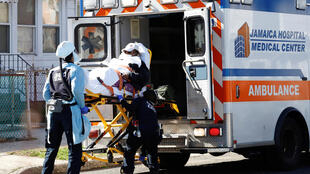 An emergency medical team transfers a patient into an ambulance in New York City, March 24, 2020.
