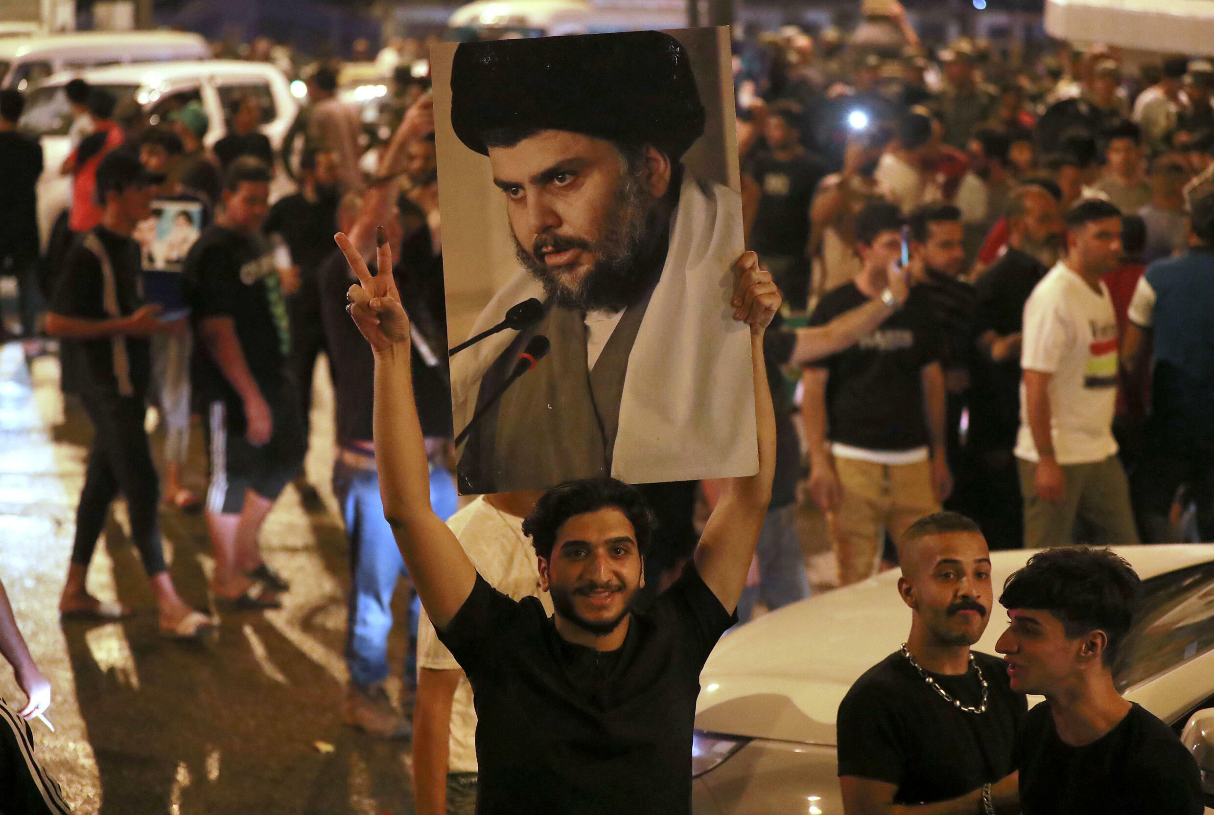 Supporters of Iraqi Shiite cleric Moqtada Sadr celebrate in Baghdad's Tahrir square on Monday after the announcement of parliamentary election results