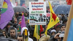 Manifestantes bajo una fuerte nevada en Múnich protestan por conflictos como la guerra en Siria y las operaciones militares de Turquía.