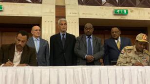 Protestataires et militaires signent un accord, entourés de médiateurs éthiopiens, le 17 juillet 2019.