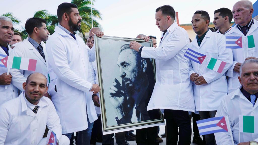 Médicos cubanos sostienen el retrato de Fidel Castro antes de partir al norte de Italia el 21 de marzo de 2020 para tratar pacientes diagnosticados con Covid-19.