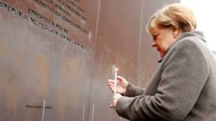 La canciller alemana Angela Merkel enciende una vela en el memorial dedicado a la época de división por el Muro de Berlín y a las víctimas de quiénes intentaron cruzarlo, en Berlín, Alemania, el 9 de noviembre de 2019.