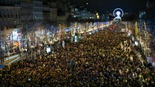 Una multitud se congrega en la avenida de los Campos Elíseos en París por las celebraciones de Año Nuevo, a principios del 1 de enero de 2018.