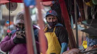 Vendedores ambulantes usan máscaras faciales como medida preventiva contra la propagación del coronavirus, en la plaza Corabastos del barrio Kennedy de Bogotá, el 28 de julio de 2020