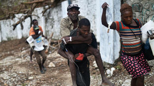 Un homme malade du Choléra, transporté à dos d'homme, dans les rues de Randelle en Haiti, le 19 octobre 2016.