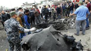Les forces de sécurité irakiennes inspectent la carcasse de la voiture piégée utilisée pour l'attentat du 8 janvier.