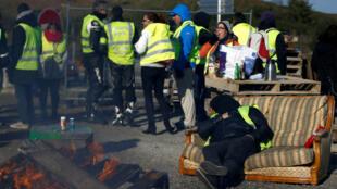 Un manifestante que usa chaleco amarillo, símbolo de la protesta de los conductores franceses contra los precios más altos del combustible, descansa mientras asiste a una protesta, en la entrada de un centro comercial en Nantes, Francia, el 19 de noviembre de 2018.
