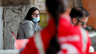 A woman wearing a protective mask waits to donate blood after appeals from hospitals and the Italian government for blood donations to help treat coronavirus patients, at an Italian Red Cross centre, in Rome, Italy March 17 2020.