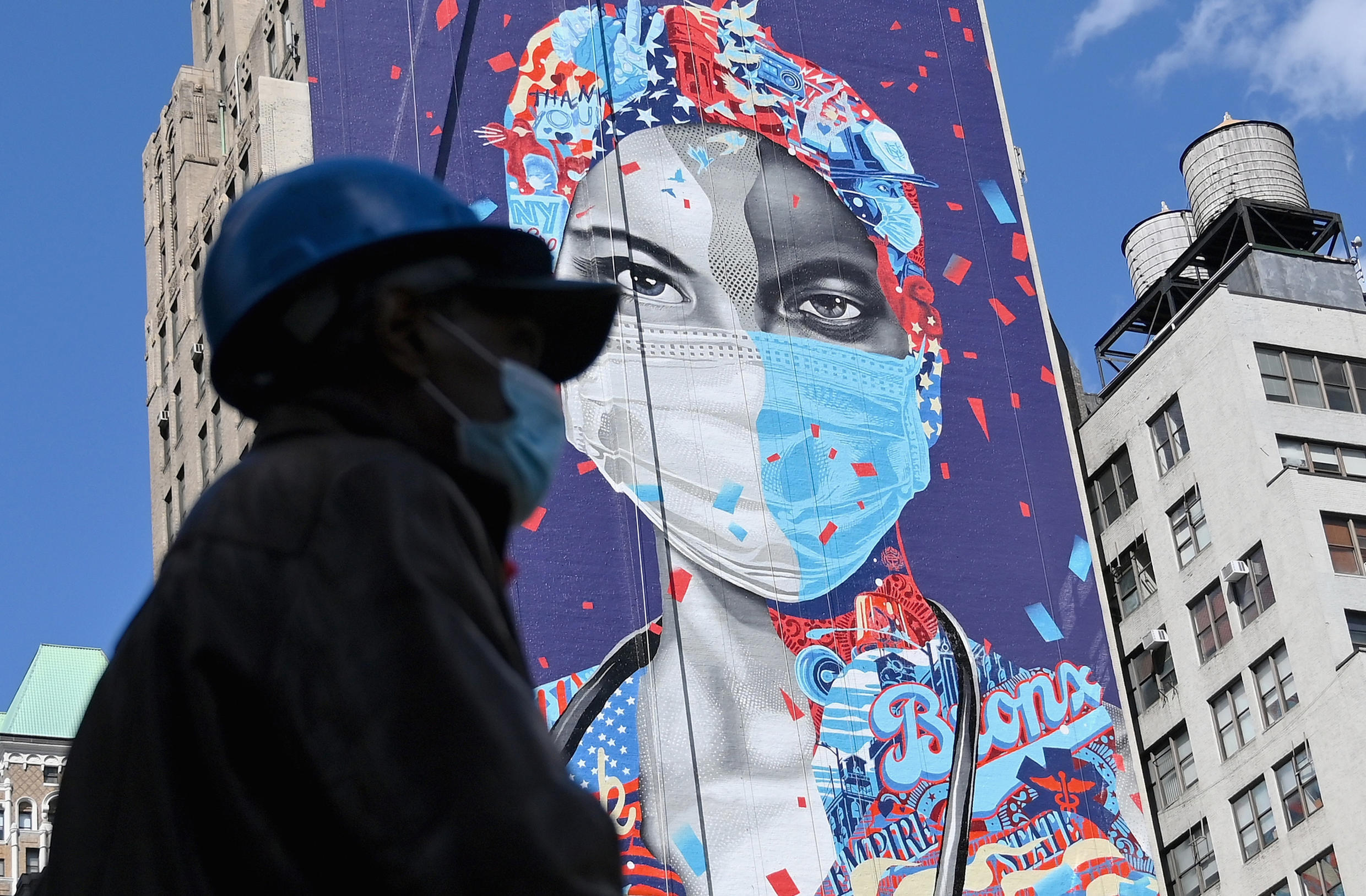 A person walks past a mural on a building on May 7, 2020 in New York City