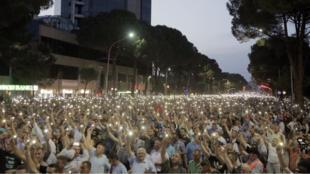 Los defensores de la oposición encienden sus teléfonos durante una protesta en Tirana, Albania, el 8 de junio de 2019.