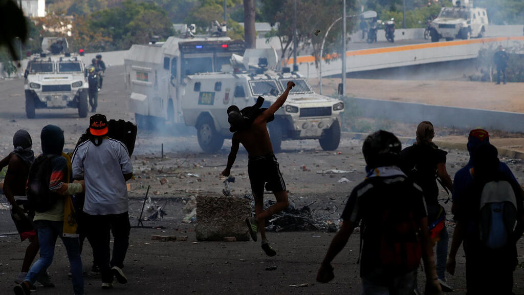 Partidarios de la oposición reaccionan frente a vehículos militares durante un mitin contra el presidente del gobierno de Venezuela, Nicolás Maduro, el 1 de mayo de 2019.