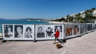 سيدة ترتدي قناعا طبيا تسير أمام صور لنجوم مهرجان كان السينمائي بالقرب من مقر المهرجان، 18 مارس/آذار 2020.
