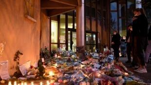 """أشخاص يقفون أمام ورود وشموع قرب لافتة كُتب عليها """"أنا أستاذ أنا صامويل"""" أمام مدرسة في كونفلان سانت - أونورين شمال غرب باريس في 17 تشرين الأول/أكتوبر 2020 تكريماً لمدرس قُتل بسبب عرضه رسوما كاريكاتورية للنبي محمد على تلاميذه"""
