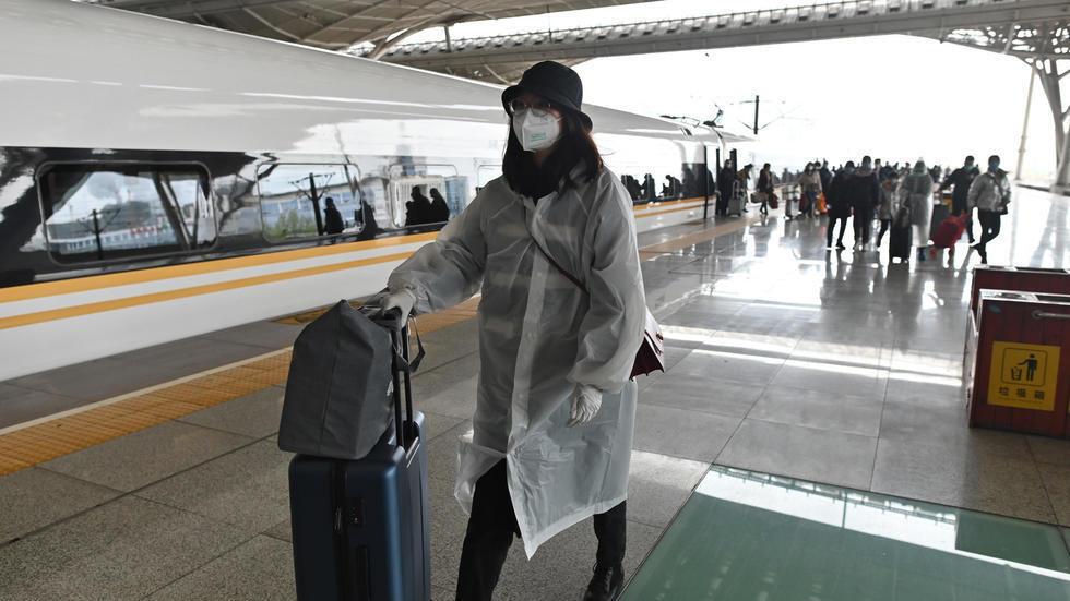 صينية تدفع أمتعتها بعد وصولها إلى محطة قطار ووهان في 28 مارس