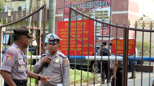 Police stand guard at the entrance of the local police headquarters following a blast in Medan, Indonesia November 13, 2019.